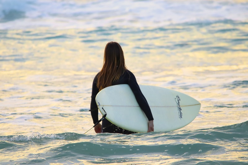 A person riding a wave on a surf board on a body of water