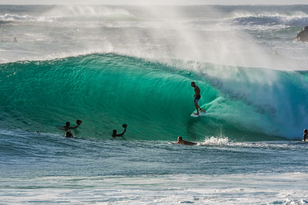 A group of people riding on top of a wave in the ocean