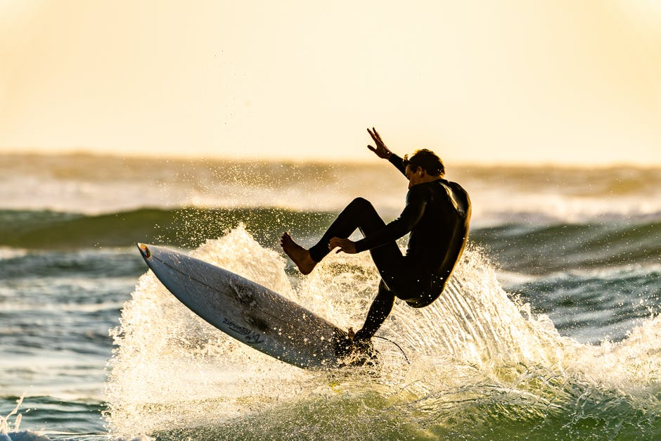 A man flying through the air while riding a wave in the ocean
