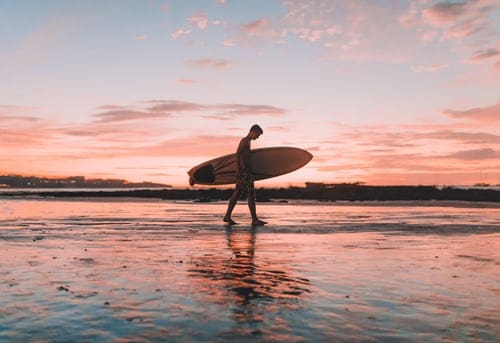 A man carrying a surf board on a body of water