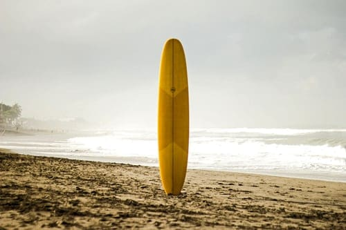 A person standing on top of a sandy beach holding a surfboard