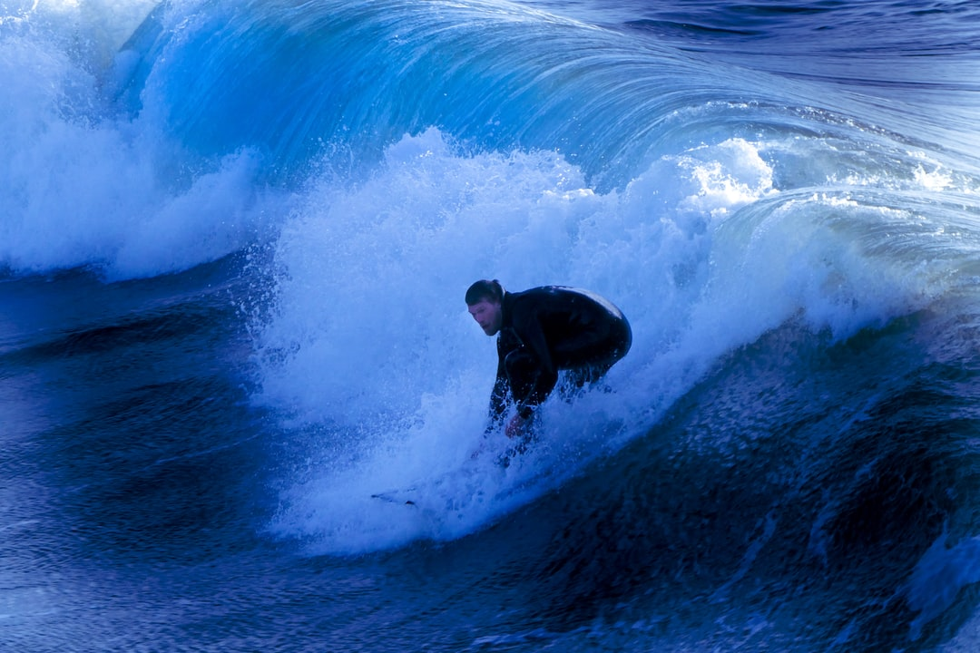 A man in a wet suit riding a wave in the ocean