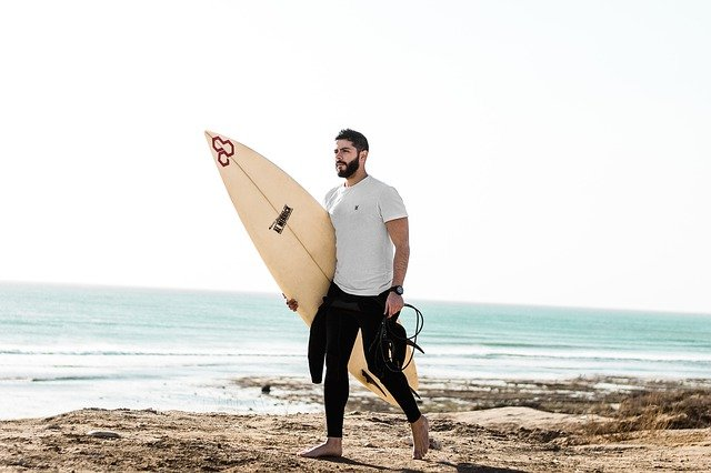 A man carrying a surf board walking on a beach