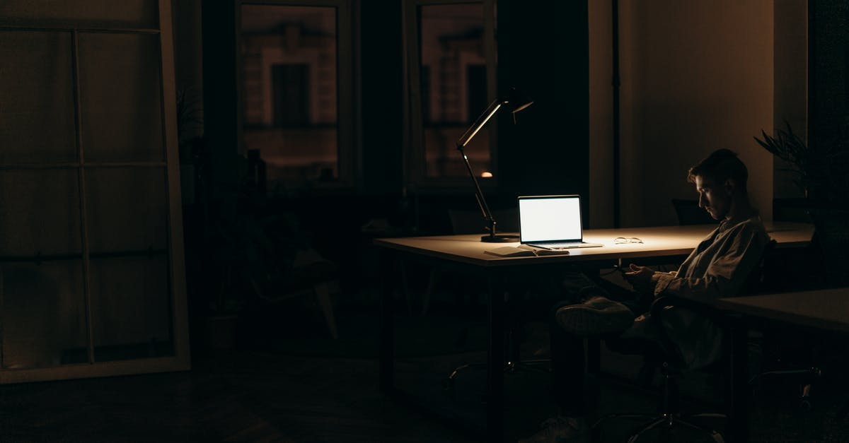 A person sitting at a desk with a laptop in a dark room