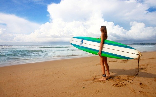 A person standing on a beach holding a surf board
