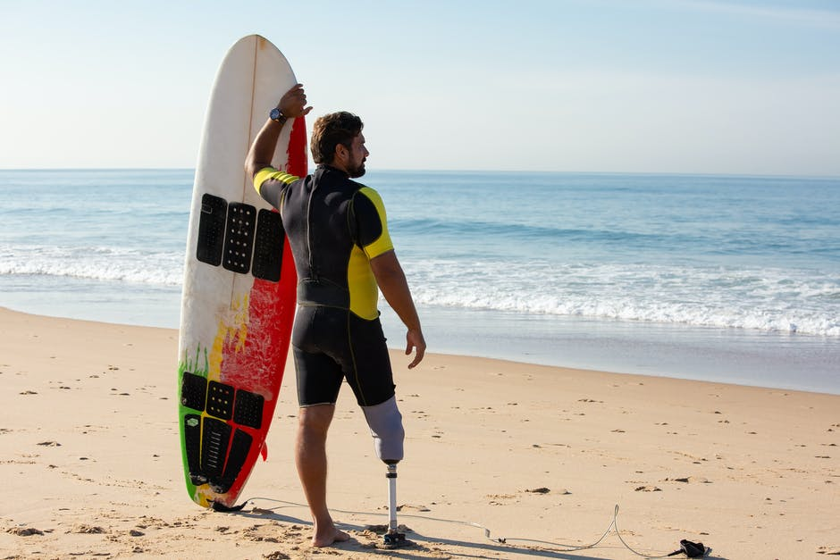 A man standing on a beach holding a surf board
